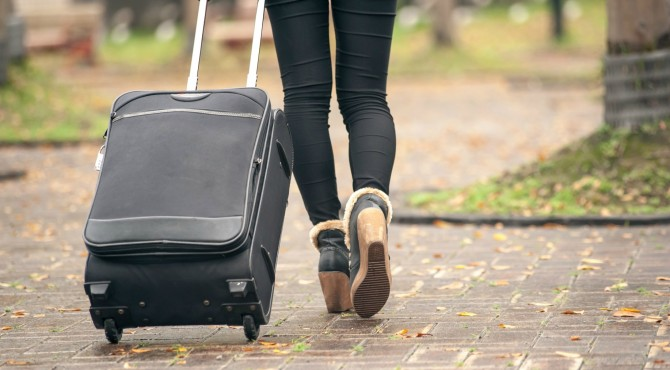 Closeup images of a woman taking a luggage in city.