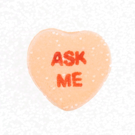 Orange candy heart that reads ask me against white background.